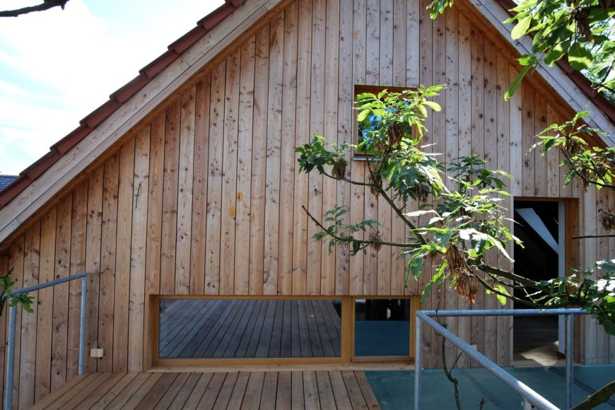 Štítová stěna mlýna byla obložena svislým modřínovým obkladem bez povrchové úpravy. Okenní rámy, byli zvoleny ve světlé barvě. Záběr je focen z terasy která navazuje na druhé patro hlavní budovy mlýna.