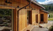 Pro možnost zabezpečení domu byly navrženy posuvné okenice na ocelových pojezdech. Ty mohou sloužit i jako zatemnění interiéru. Na fotce jsou už klasicky zkombinována otevíravá a fixní okna. Hlavní vstup do domu je doplněn o zádveří což majitel ocení hlavně v zimním období.