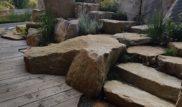 Na fotce můžeme vidět napojení modřínové terasy na kamenné schody,které jsou provedeny z velkých vápencových bloků. Před použitím lomového kamene pro dlažbu,sokl, nebo opěrnou zídku je vždy vhodné si ověřit zkušenosti jiných stavebníků s daným materiálem. V tomto případě byl zvolen lomový kámen ze Slovenska, který není vhodný např. na pojezd vozidel protože je měkčí a při větším zatížení praská
